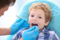 Examen pédiatrique de dentiste petites dents bouclées de garçons dans la chaise de dentistes à la clinique Traitement et examens  photographie stock libre de droits
