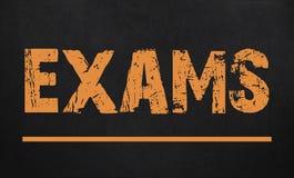 Examens /are écrits sur un tableau Tableau noir Photos stock