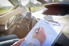 Examinador que completa formulario de la prueba en carretera de la licencia del ` s del conductor fotografía de archivo libre de regalías