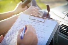 Examinador que completa formulario de la prueba en carretera de la licencia del ` s del conductor Fotos de archivo libres de regalías