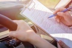 Examinador que completa formulario de la prueba en carretera de la licencia del ` s del conductor Imagen de archivo libre de regalías