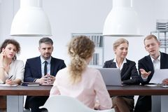 Examination board discussing resume. Members of examination board discussing woman`s resume royalty free stock images