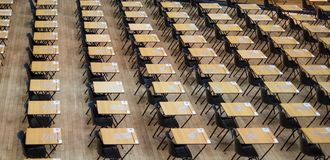 Examination hall set up with chairs and wooden desks. Photographed at Queen Mary, University of London. Mile End UK royalty free stock images