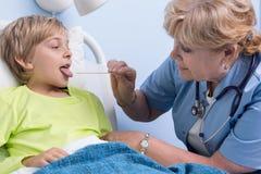 Examination of the throat. Of ill boy Stock Photos
