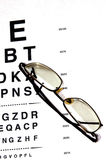 Examine eyes. Modern eyeglasses resting on eyechart with frame closed Royalty Free Stock Photo