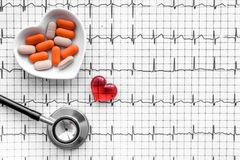 Examine the heart to prevent heart disease. Heart sign, pills and stethoscope on cardiogram background top view Royalty Free Stock Photos
