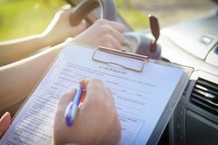 Examiner filling in driver`s license road test form Royalty Free Stock Photos