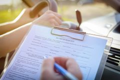 Examiner filling in driver`s license road test form Stock Photo