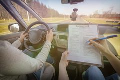 Examiner filling in driver`s license road test form. Sitting with her student inside a car stock image