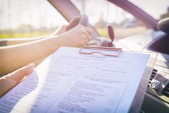 Examiner filling in driver`s license road test form