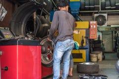 Examiner une roue de voiture pour assurer la réparation au garage de voiture Photographie stock libre de droits