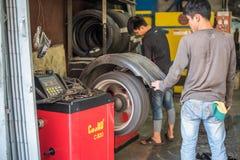 Examiner une roue de voiture pour assurer la réparation au garage de voiture Image libre de droits