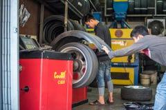 Examiner une roue de voiture pour assurer la réparation au garage de voiture Images libres de droits