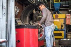 Examiner une roue de voiture pour assurer la réparation au garage de voiture Photos stock