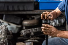 Examiner une suspension de voiture pour assurer la réparation au garage de voiture photographie stock libre de droits