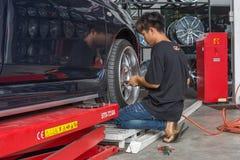 Examiner une suspension de voiture pour assurer la réparation au garage de voiture Photographie stock