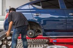Examiner une suspension de voiture pour assurer la réparation au garage de voiture Images stock