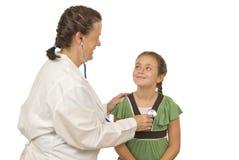 Examines Smiling医生小女孩 免版税图库摄影