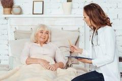 Examinig femenino positivo profesional del doctor su paciente en casa imagen de archivo
