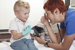 Examining医生逗人喜爱的小男孩 免版税库存照片