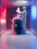 Examining bio hazardous waste in containment tent. Person in a protective suit and gas mask working with steaming substances over a blue waste drum marked as bio royalty free stock photo