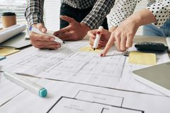 Examining building plan. Close-up image of architects working on building plan Royalty Free Stock Photo
