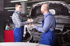 Examining car for damage in workshop. Happy insurance agent and professional mechanic indoors in workshop are examining a car after incident for front end damage Royalty Free Stock Photo