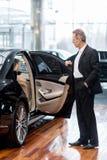 Examining car at dealership. Stock Photos