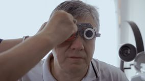 Examining eyesight with optical trial frame. Doctor check man`s sight with optical trial frame. Senior man has a bad eyesight and check it in ophthalmologist in stock footage