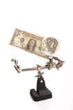 Examining finances. Photograph of a small tool holding a magnifying glass and looking at a single dollar bill Royalty Free Stock Photography