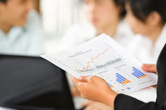 Examining graphs with other people on background Royalty Free Stock Images