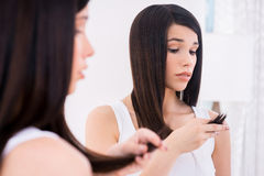 Examining her damaged hair. Stock Images