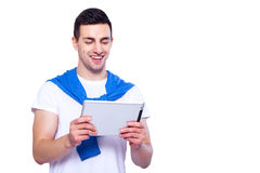 Examining his brand new gadget. Handsome young man holding digital tablet and looking at it with smile while standing against white isolated background Stock Photography