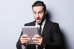 Examining his brand new tablet. Royalty Free Stock Image