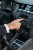 Examining his new car. Close-up of man in formalwear touching dashboard with finger while sitting in car Stock Image