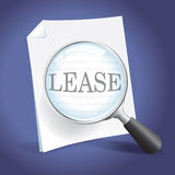 Reviewing a Lease Agreement. Examining a Lease Agreement with a Magnifying Glass Royalty Free Stock Image