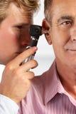 Examining Male Patient的Ears医生 免版税库存图片