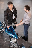 Examining motorcycle. Cheerful young sales executive consulting. Customer about motorcycle Royalty Free Stock Image