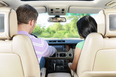 Examining a new car. A young couple is examining a side panel of the car stock photography