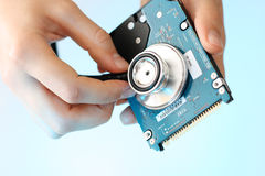 Examining notebook's HDD with stethoscope. Doctor holding stethoscope in her fingers against a back side of the notebook harddisk Royalty Free Stock Image