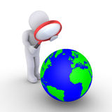 Examining the planet. Person is looking through magnifier at the globe Royalty Free Stock Images