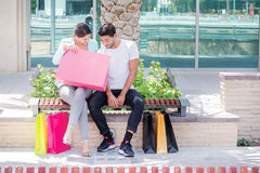 Examining purchases. Couple sitting on a bench and holding shopp Royalty Free Stock Image