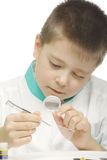 Examining specimen. Young school scientist examining specimen with magnifier Royalty Free Stock Image