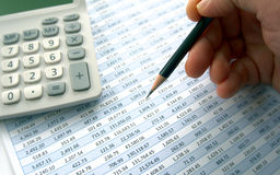 Examining spreadsheet with calculator. Analyzing figures on spreadsheet with calculator Stock Photo