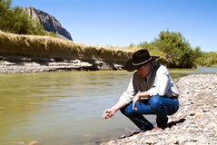 Examining the Terrain. A man dressed in western garb squatting beside a river examining the terrain stock image