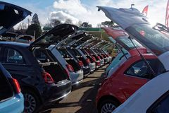 Garage Forecourt with Cars Displayed for Sale. Example of a car showroom forecourt with rows of automobiles lined up for sale, and with boots, or trunks, open Royalty Free Stock Image