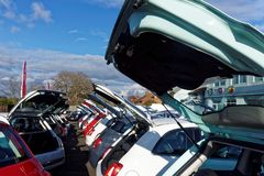 Garage Forecourt with Cars Displayed for Sale. Example of a car showroom forecourt with rows of automobiles lined up for sale, and with boots, or trunks, open Royalty Free Stock Photos