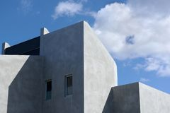 Architectural detail of a modern concrete residential building against a cloudy blue sky. royalty free stock photography