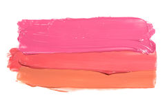 Examples of different shine lip glosses flowing downwards on a white background Stock Photo