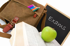 Exams. Satchel and books next to a blackboard with the word exams Stock Photos